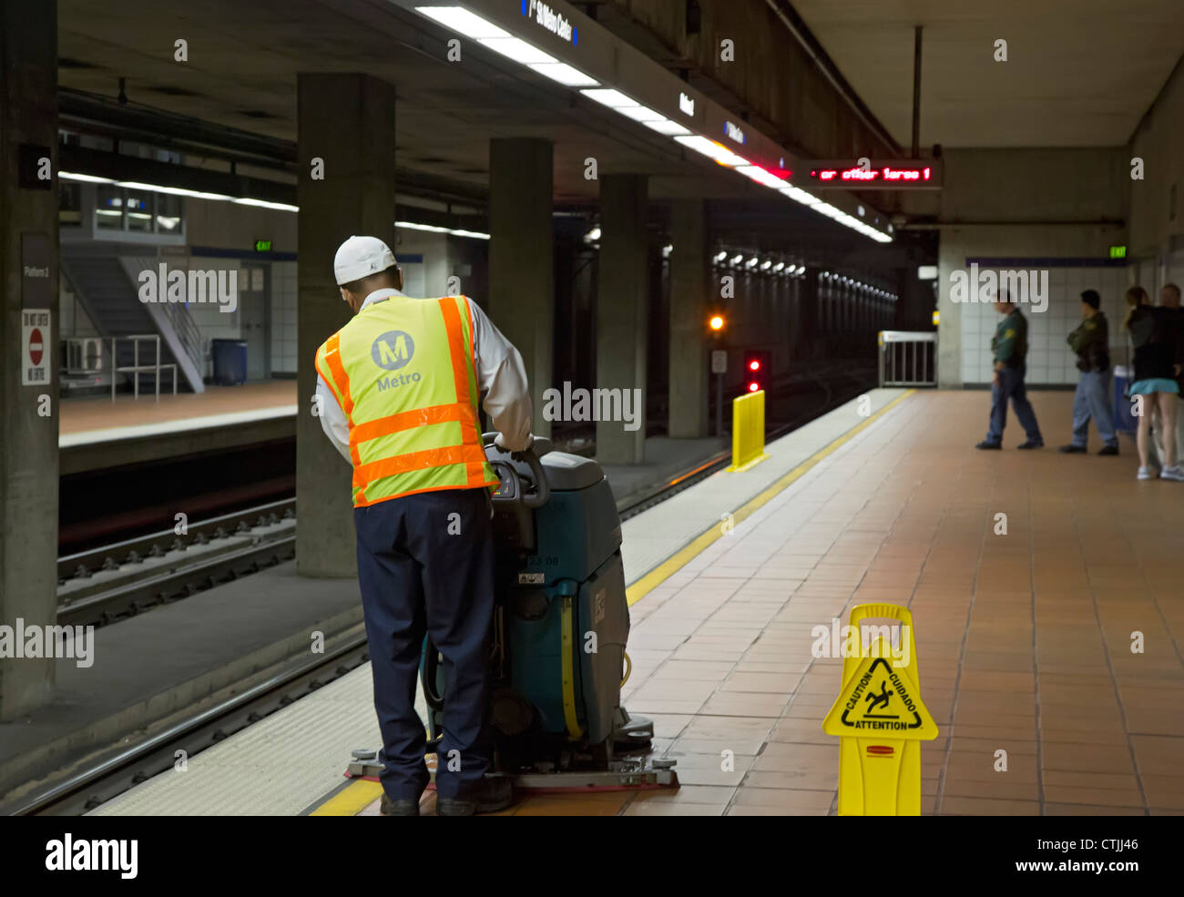 Los Angeles, California - A worker cleans the platform in a subway station of the Los Angeles Metro rail system. - Stock Image