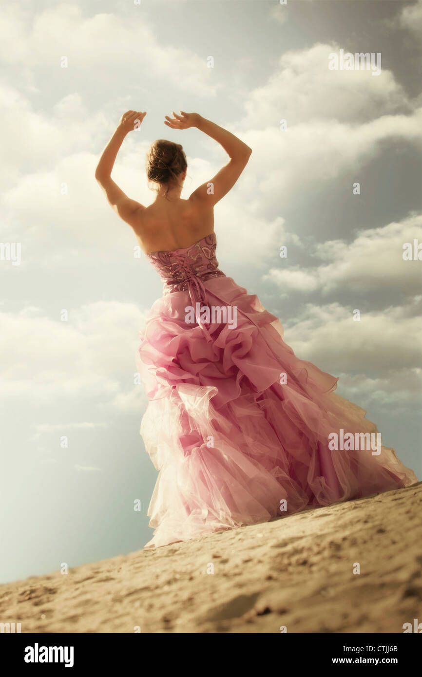 a woman standing on the beach in an evening dress - Stock Image
