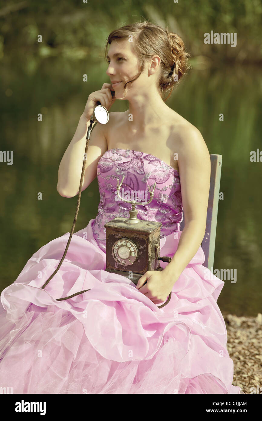a woman phones outside in evening dress - Stock Image