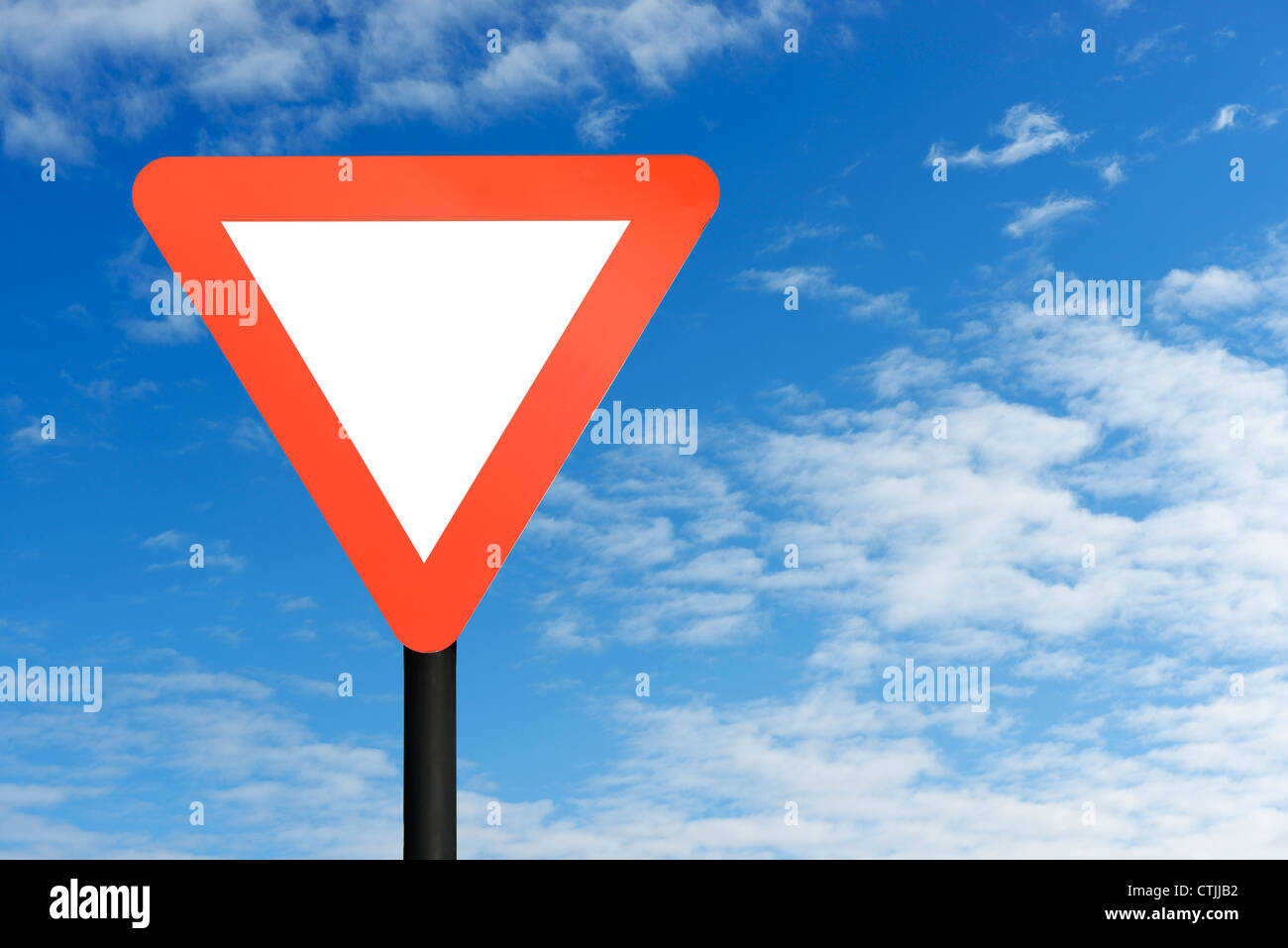 Red blank triangular road sign and blue sky - Stock Image