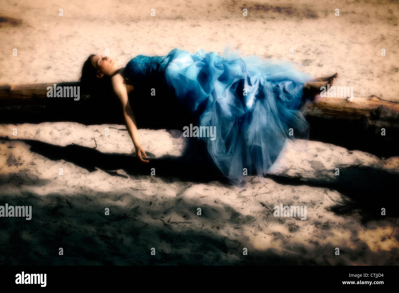 a woman in evening dress lying on a tree trunk - Stock Image
