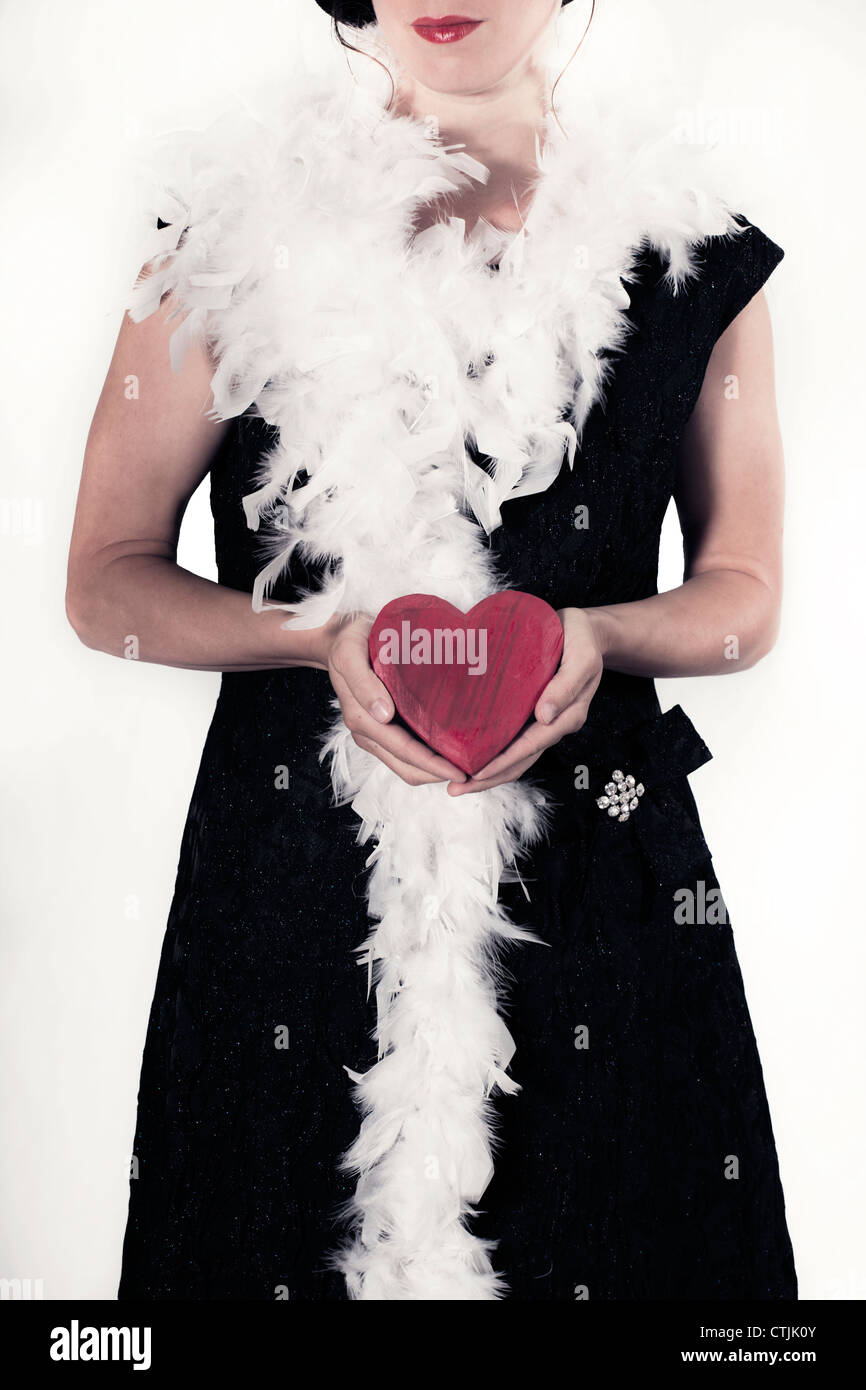 a woman in a black dress with a feather boa holds a red heart in hands - Stock Image