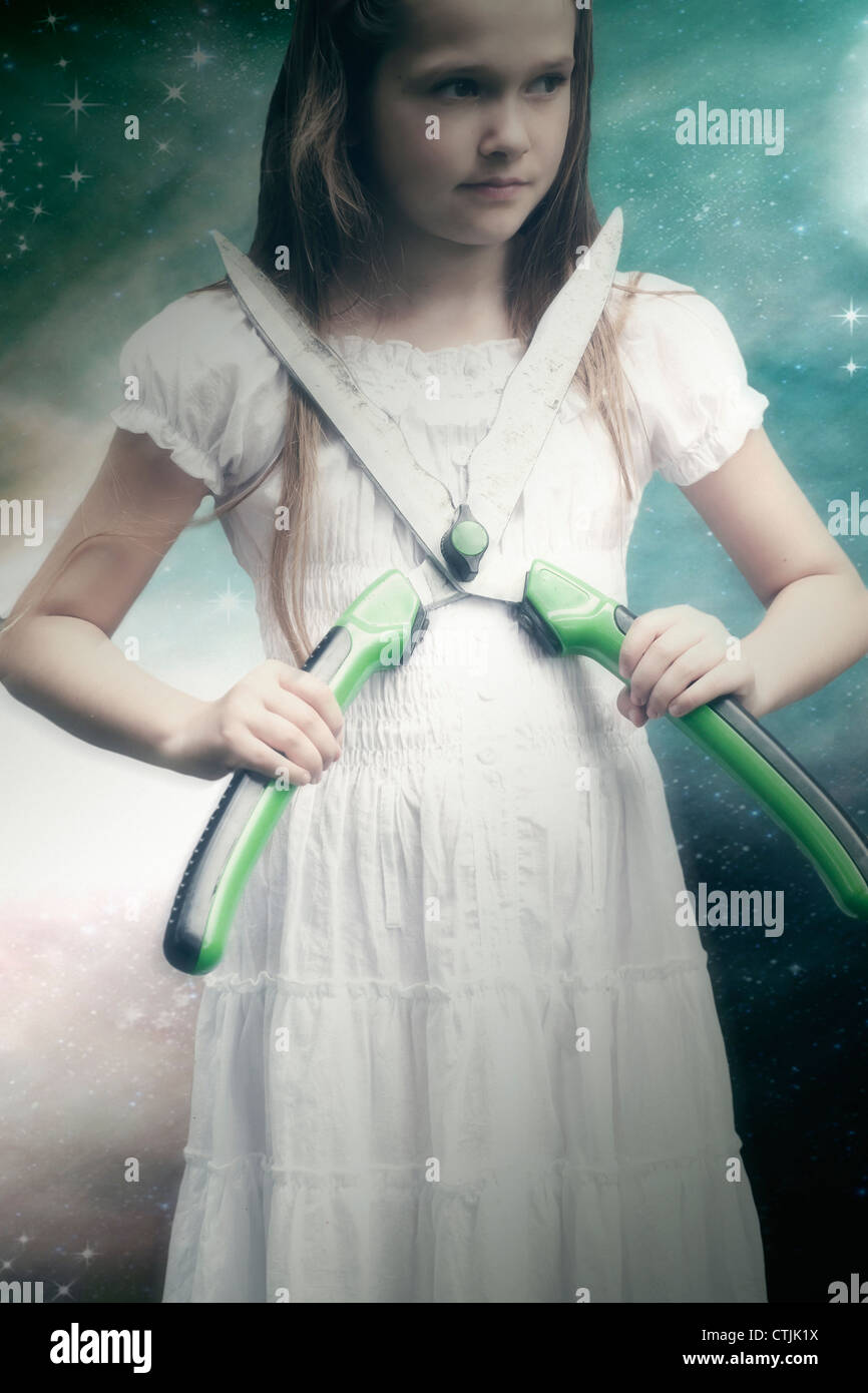 Girl in white dress holding large hedge clippers in her hands - Stock Image