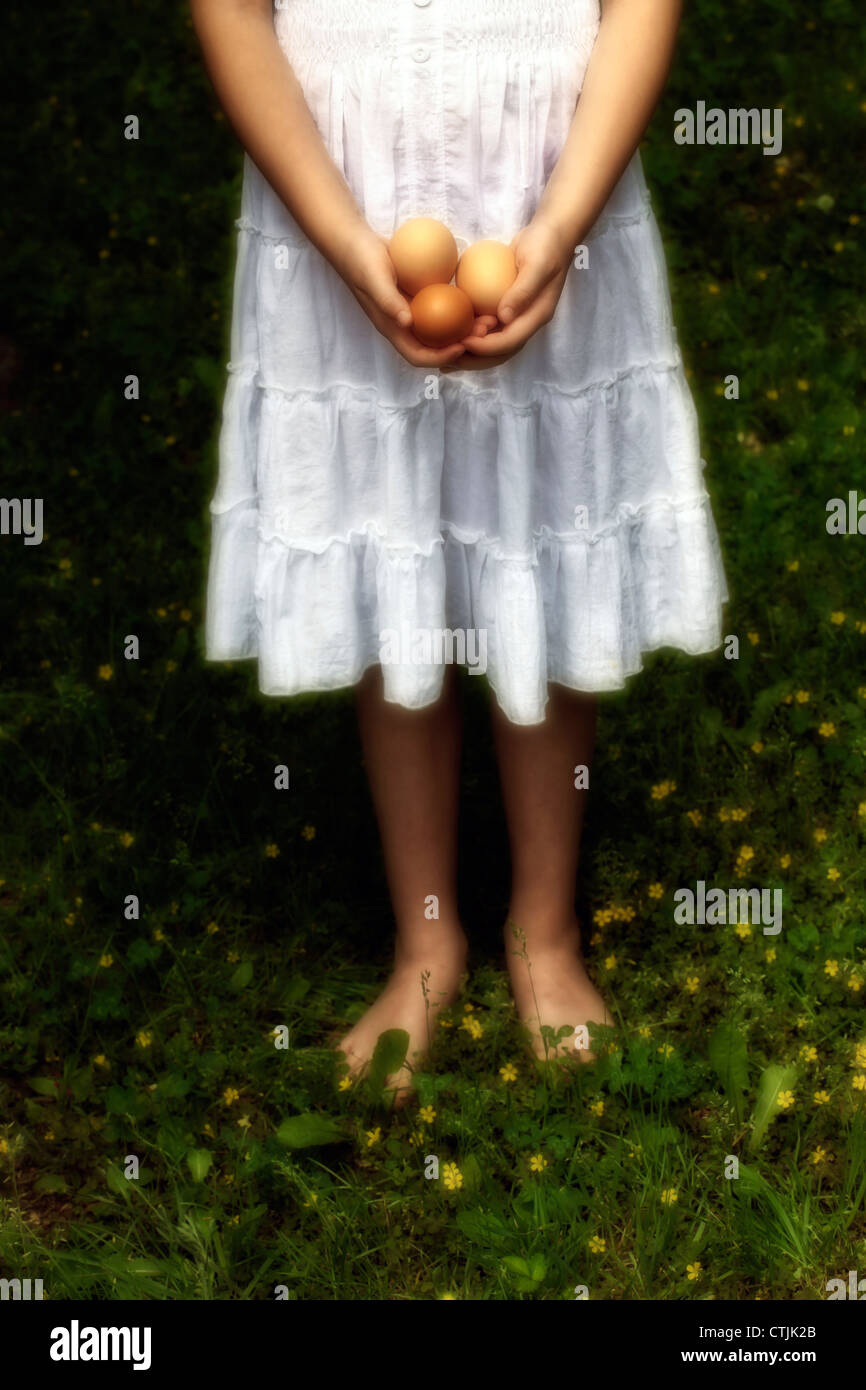 Girl is standing barefoot on grass and holds three raw eggs in her hands - Stock Image