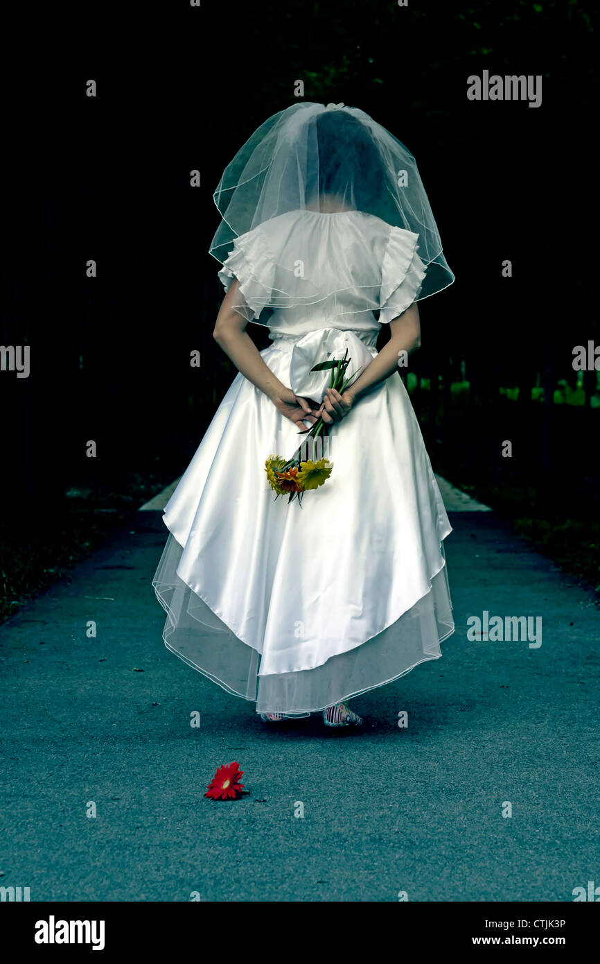 a woman in a wedding dress is walking through a dark alley - Stock Image