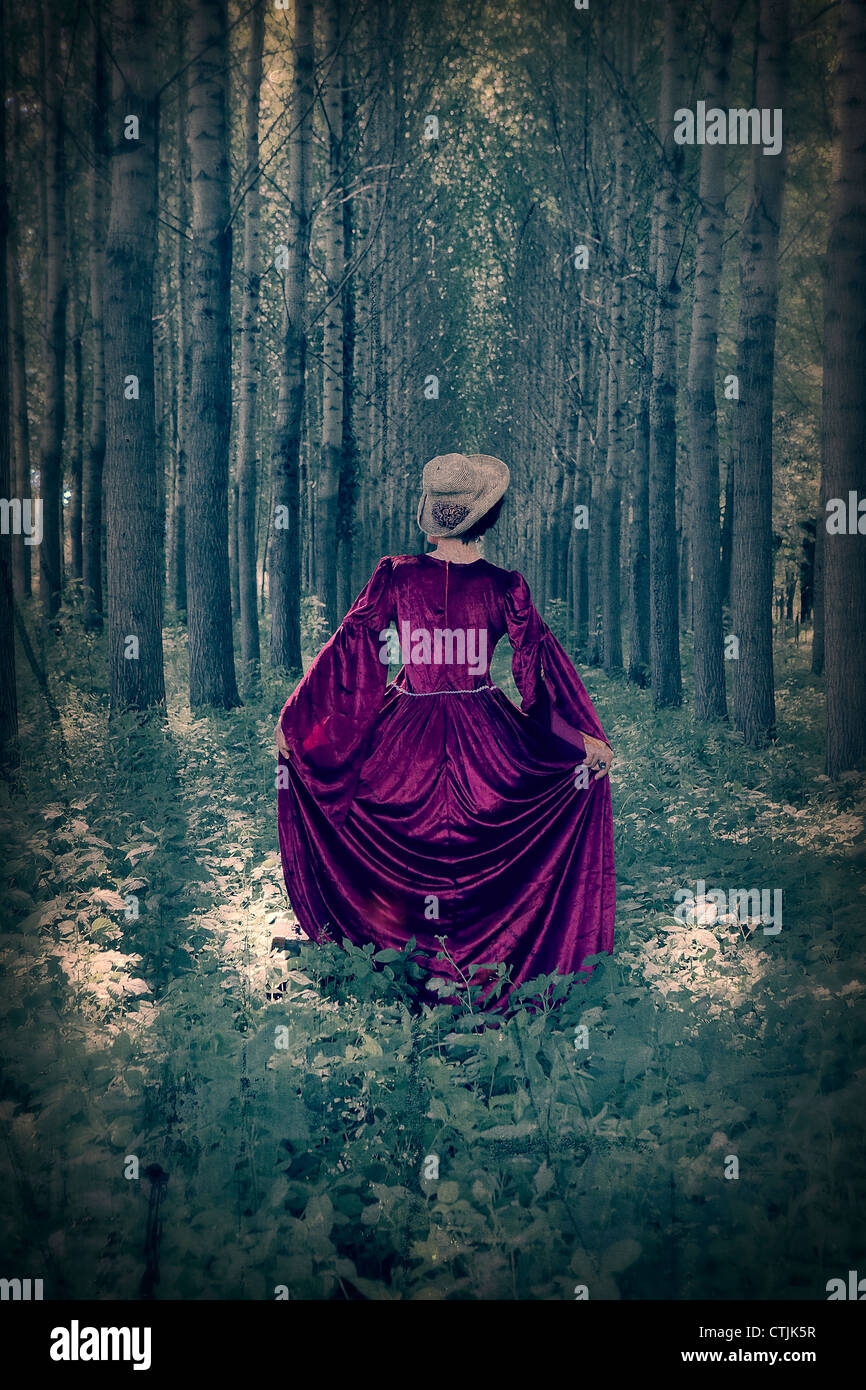 a woman with a period dress standing in a forest - Stock Image