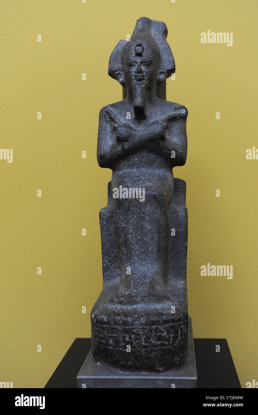 Statuette of Osiris wearing crown and royal scepters in their hands. Granite. - Stock Image