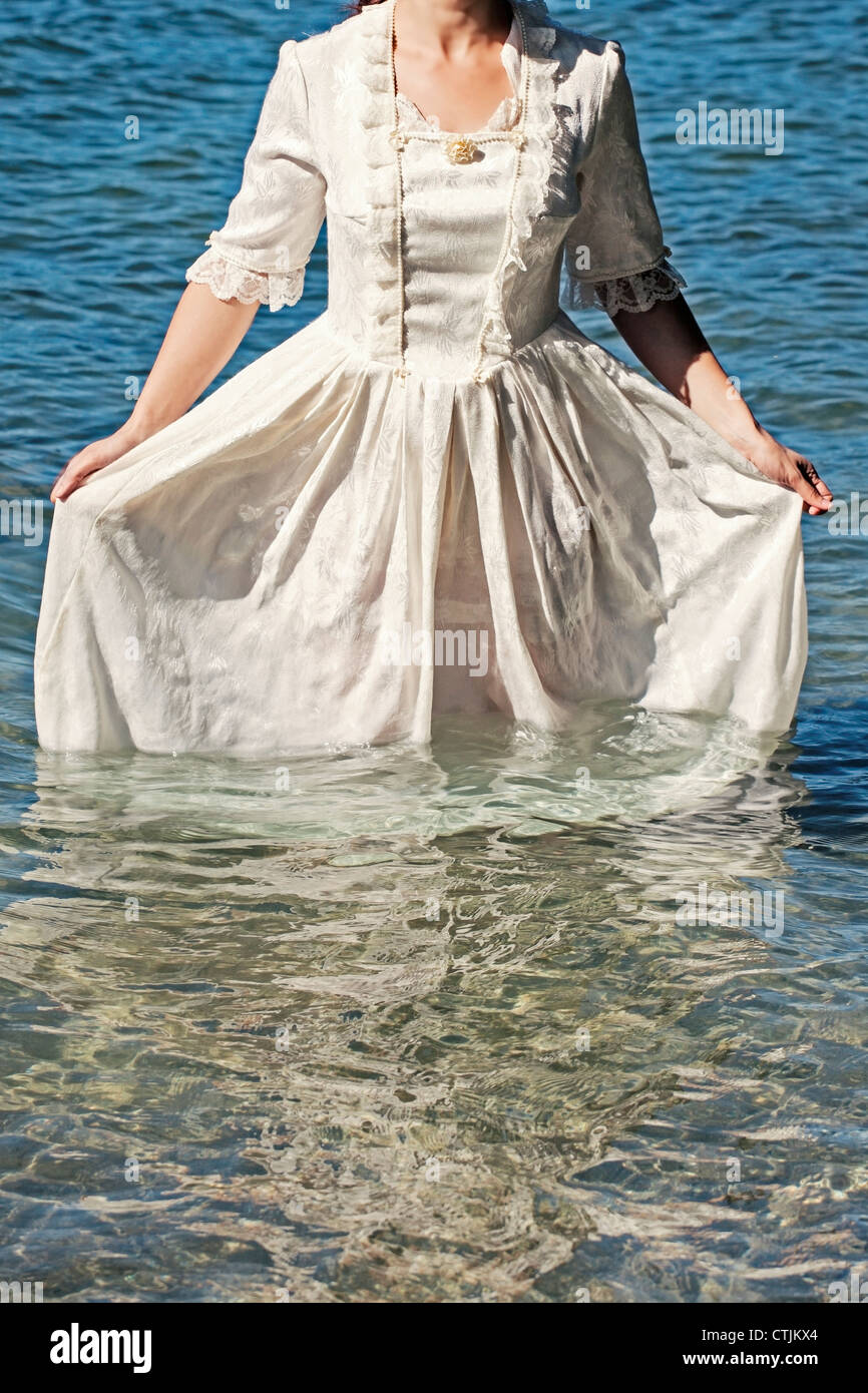 a woman in a white, Victorian dress standing in the water Stock Photo