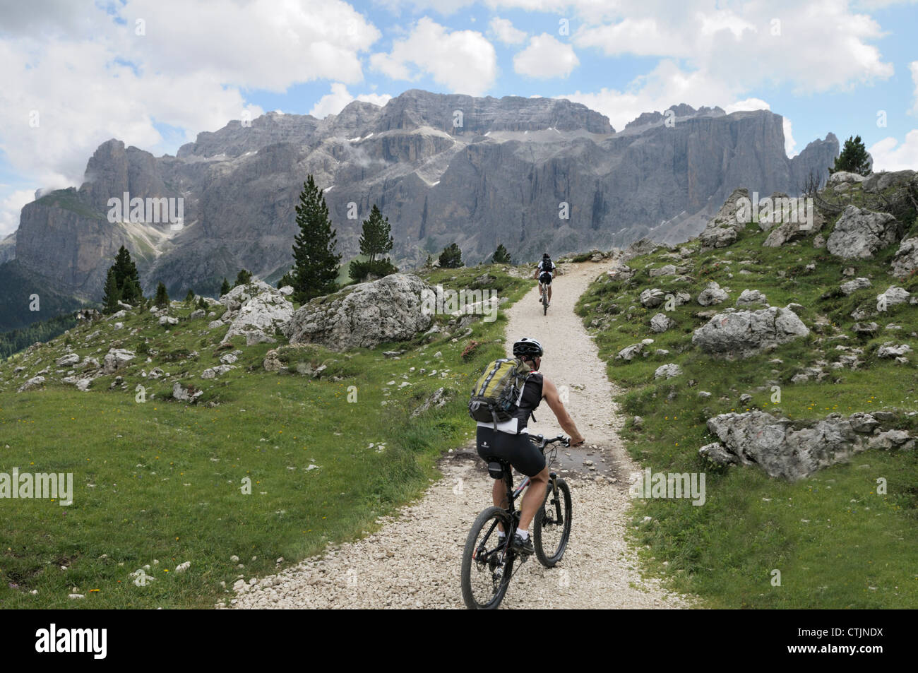 Mountain biking towards the Sella Massif in the Dolomites near Sella Pass - Stock Image