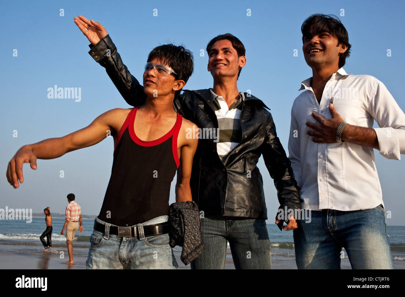 A group of young Indian holidaymakers on Nagoa Beach in Diu, India. - Stock Image