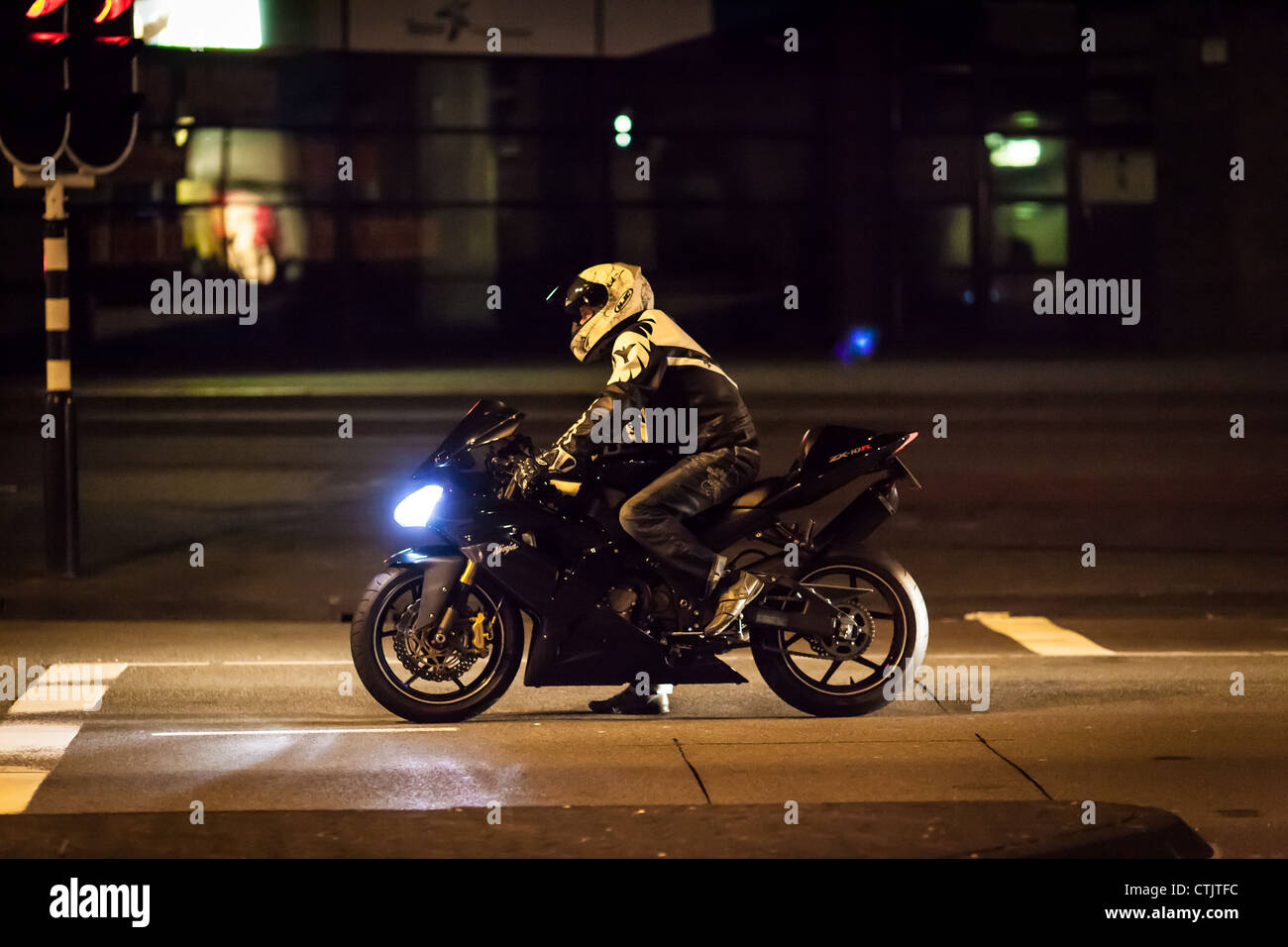 motorcycle waiting in front of stoplight at night - Stock Image