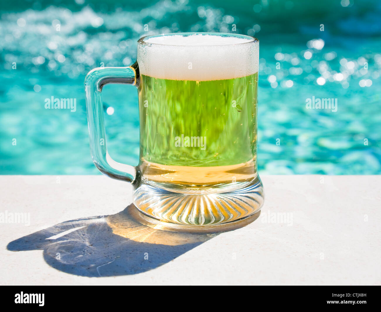 glass of cold beer on pool board in hot summer day - Stock Image