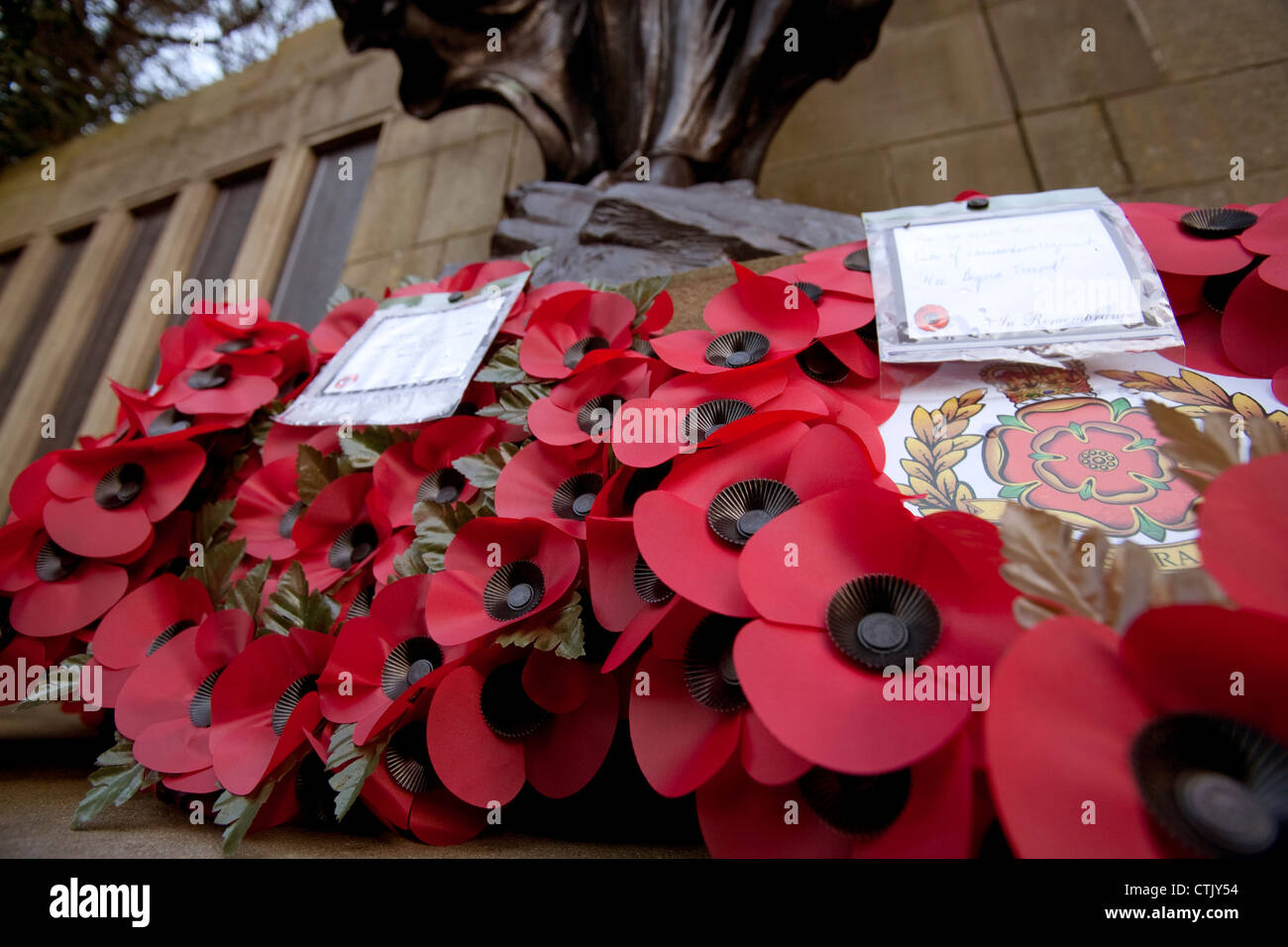 Poppy wreaths at a war memorial on Armistice Day in an English town - Stock Image