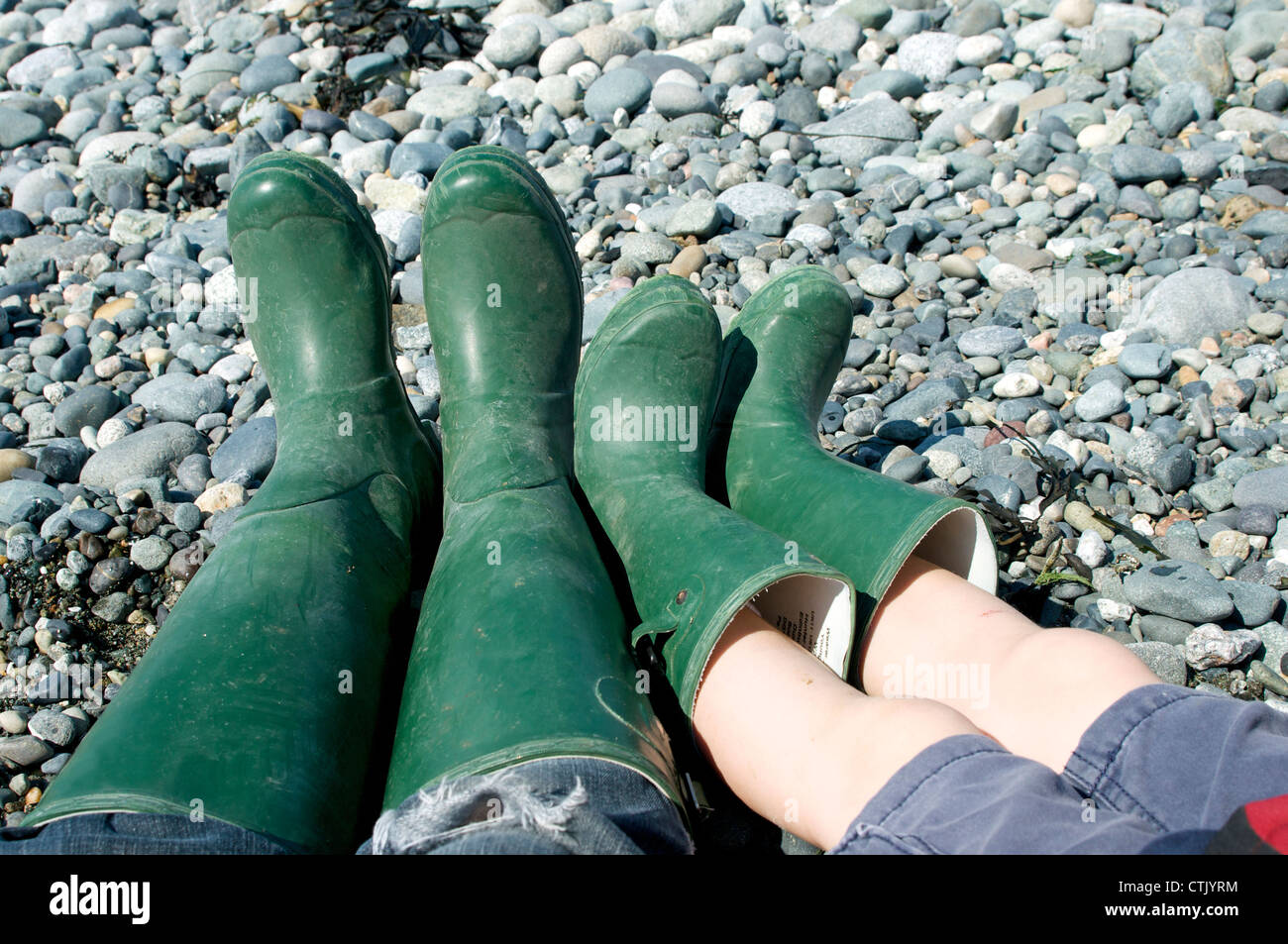 Mother and child both wear a pair of green wellingtons on a rocky beach - Stock Image