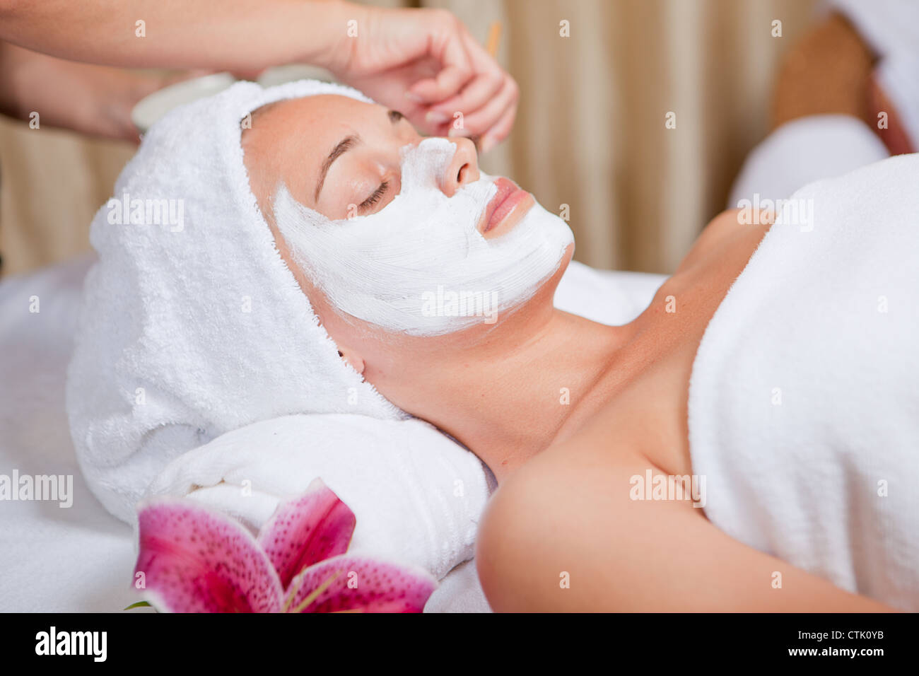 skin care, beautician applying face mask cream - Stock Image