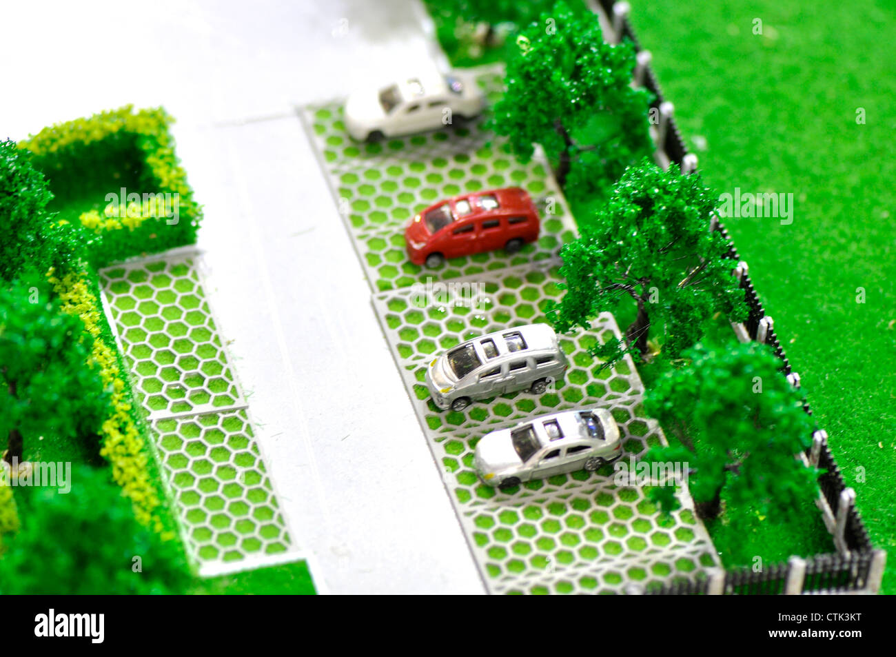 model of parking place with several cars, grass and tree,  - Stock Image