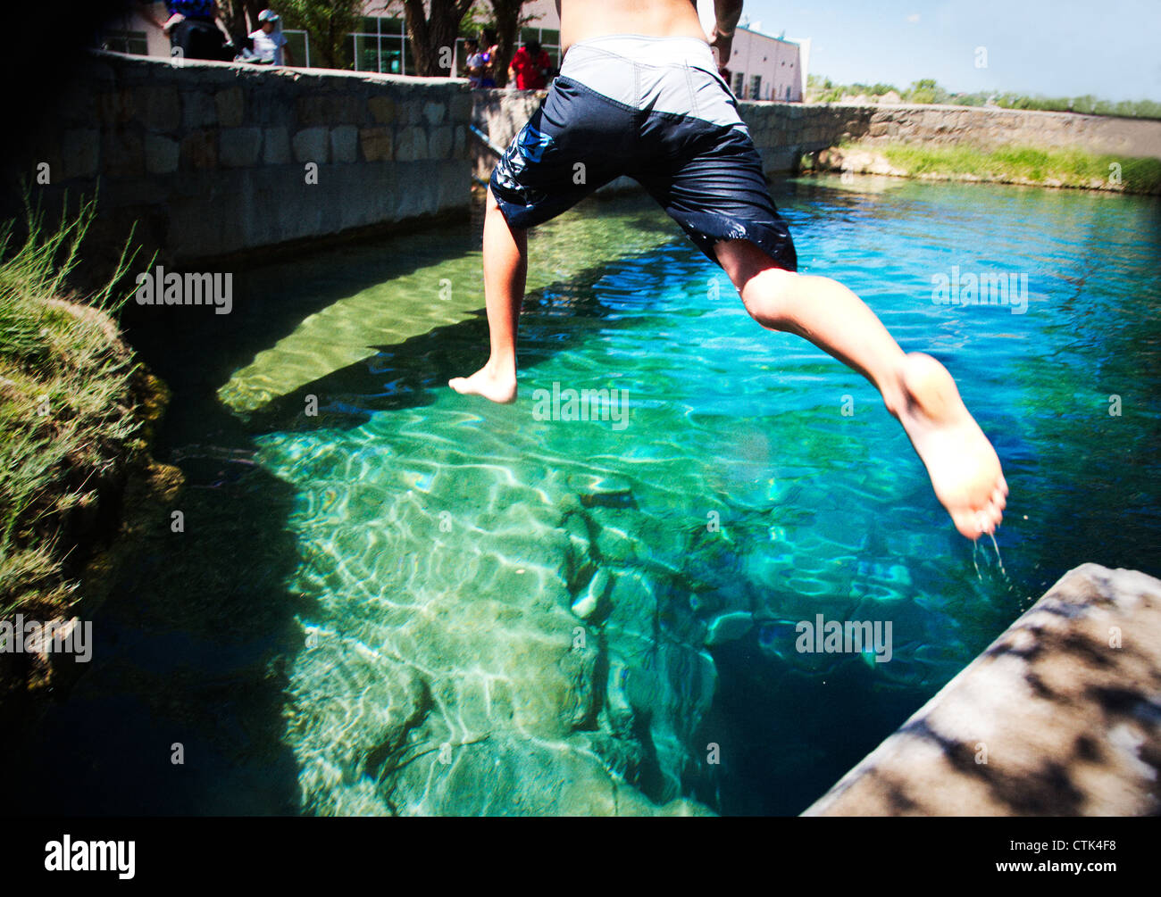 Twelve year old boy jumping into deep blue water at The Blue Hole, Santa Rosa, New Mexico. - Stock Image