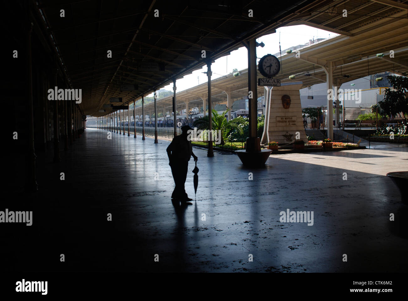An old man with an umbrella walks through Sirkeci railway station in Istanbul. Picture by: Adam Alexander/Alamy - Stock Image