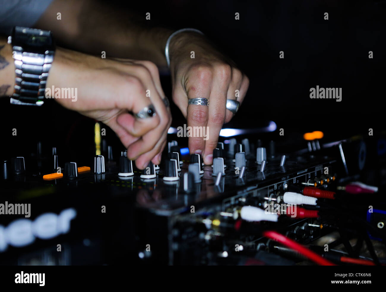 Dj turns dials - Stock Image