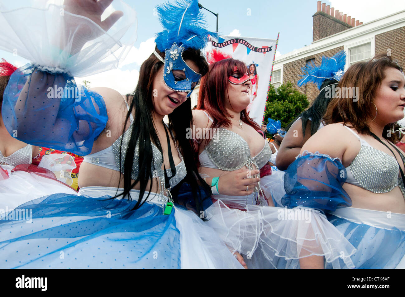 Hackney carnival parade .Young buxom women parade proudly in bra tops ,taffeta skirts and feather headresses - Stock Image