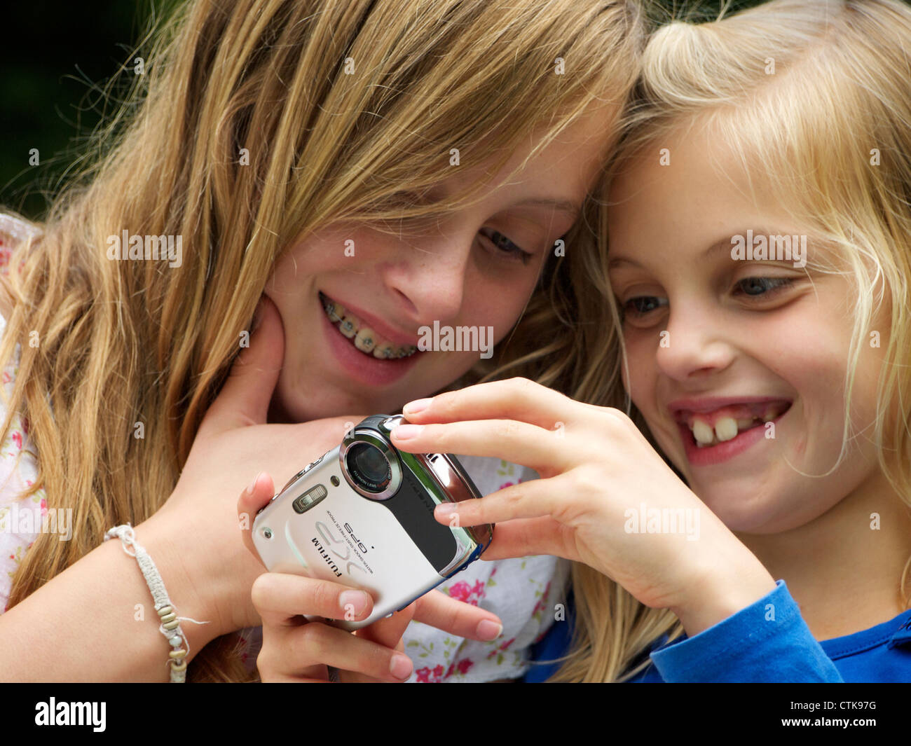 Two young girls sisters smiling while looking at pictures on their digital camera - Stock Image
