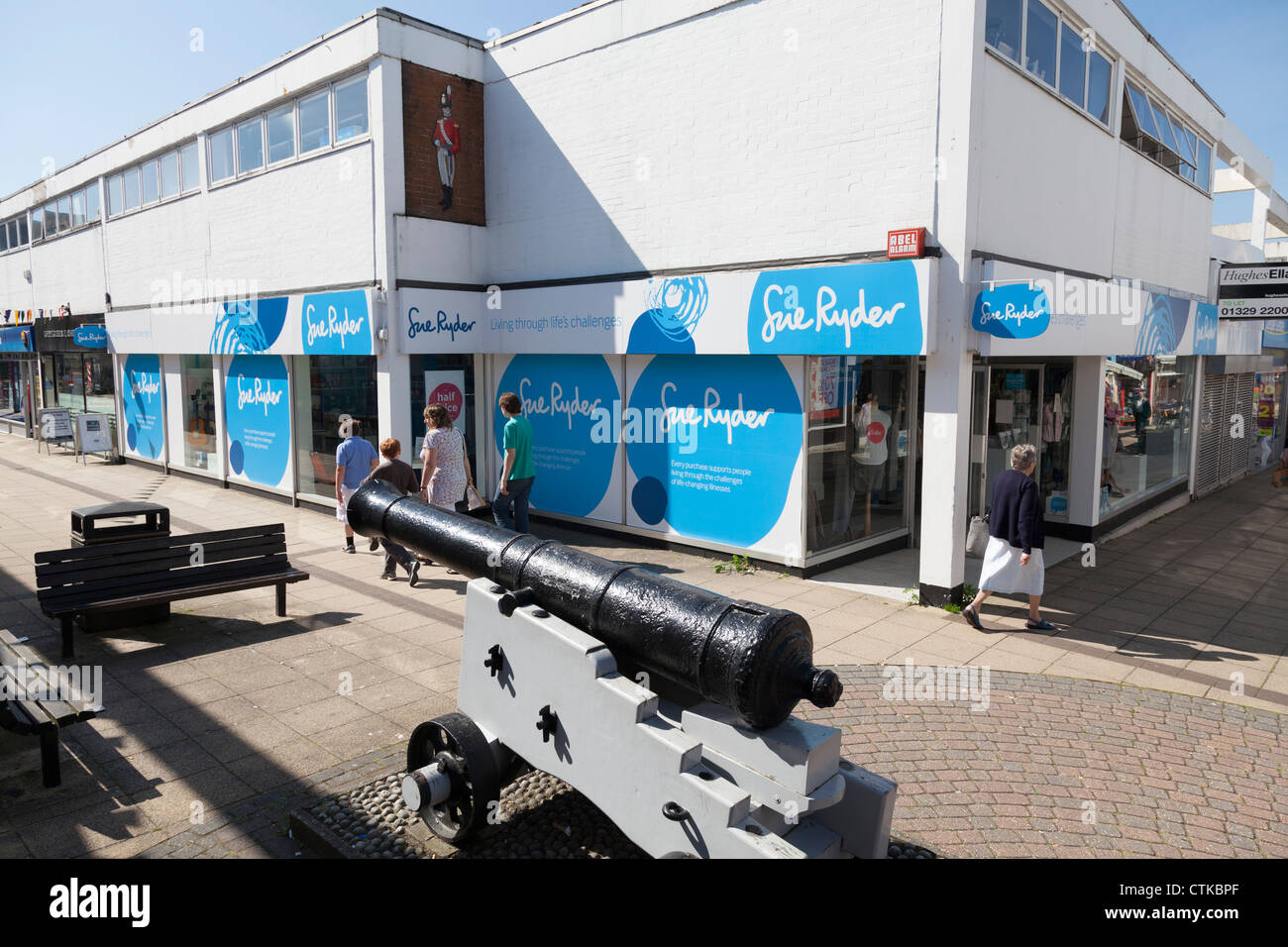 Sue Ryder charity shop in town centre arcade with canon in foreground - Stock Image
