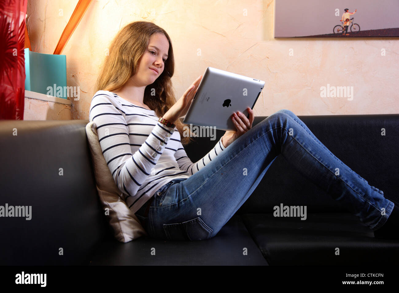 Young girl at home, using an IPad, tablet computer ...