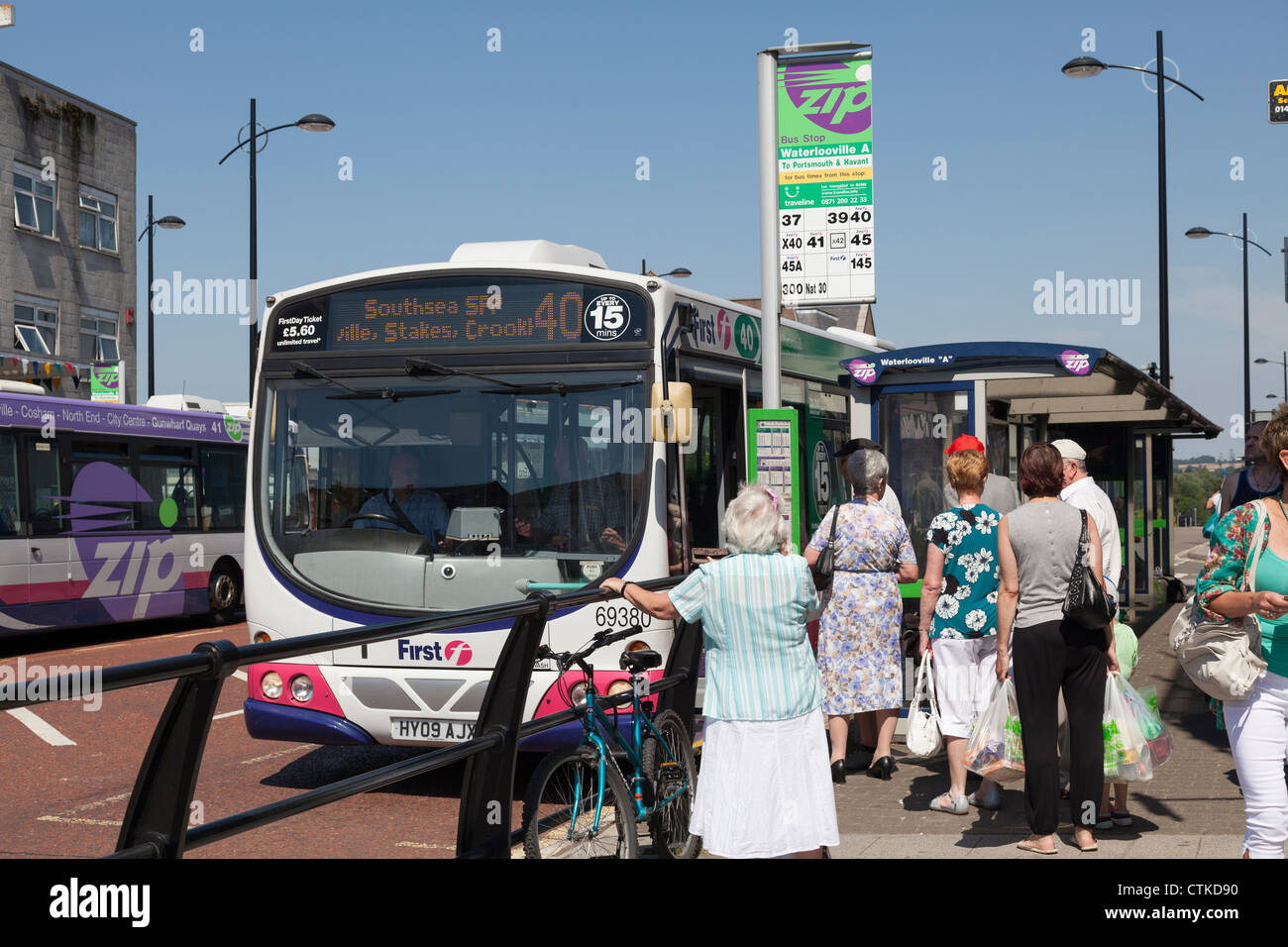 Passengers queing and boarding single decker bus at bus stop - Stock Image