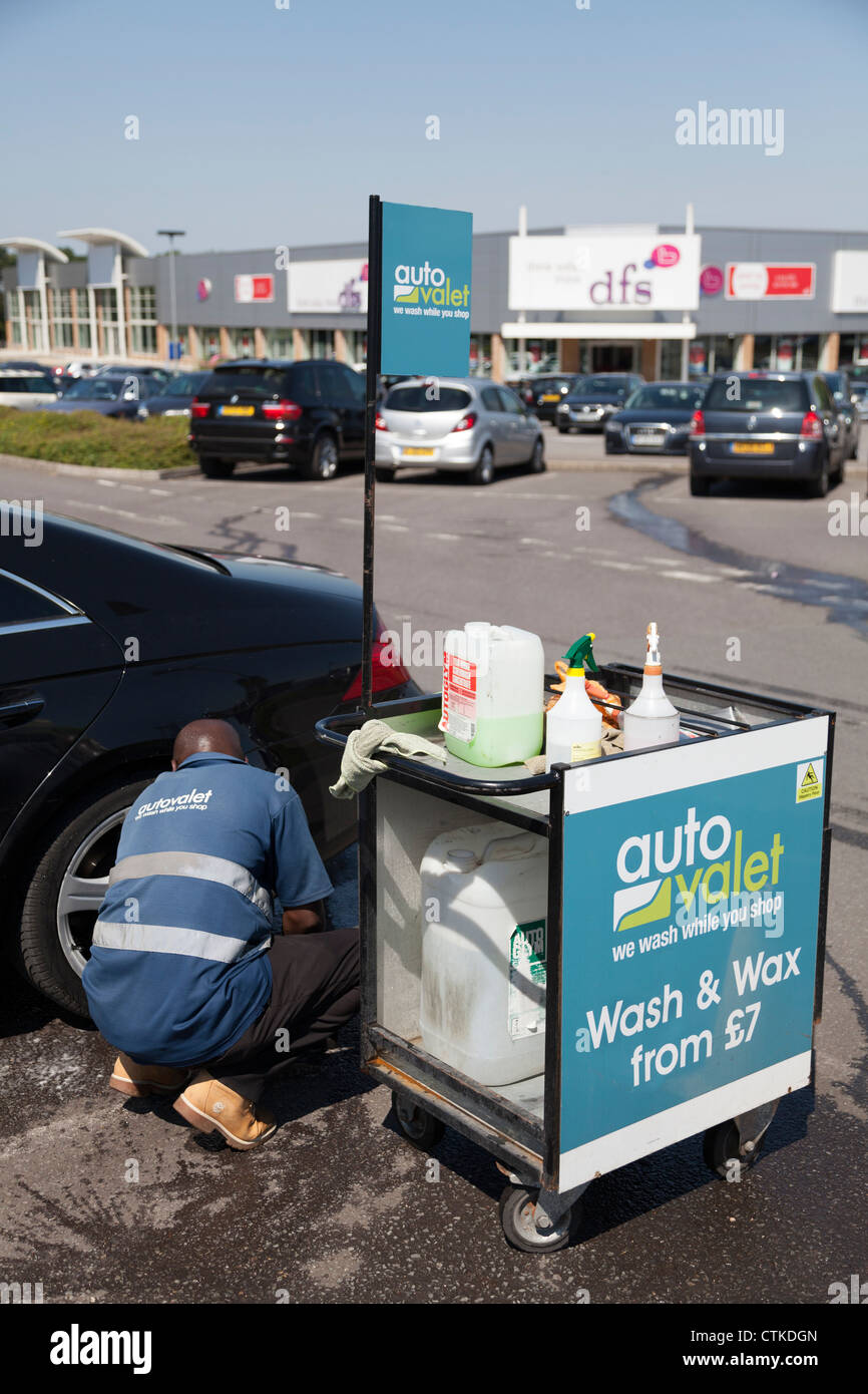 Man operating car park car wash and valet service cleaning car. - Stock Image