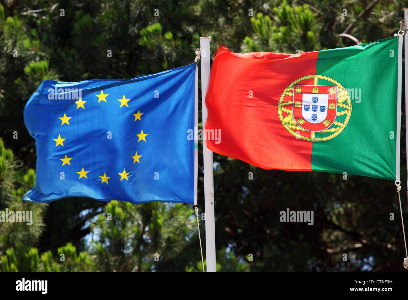 The flags of the European Union (left) and Portugal (right) fly in Lisbon, Portugal. - Stock Image