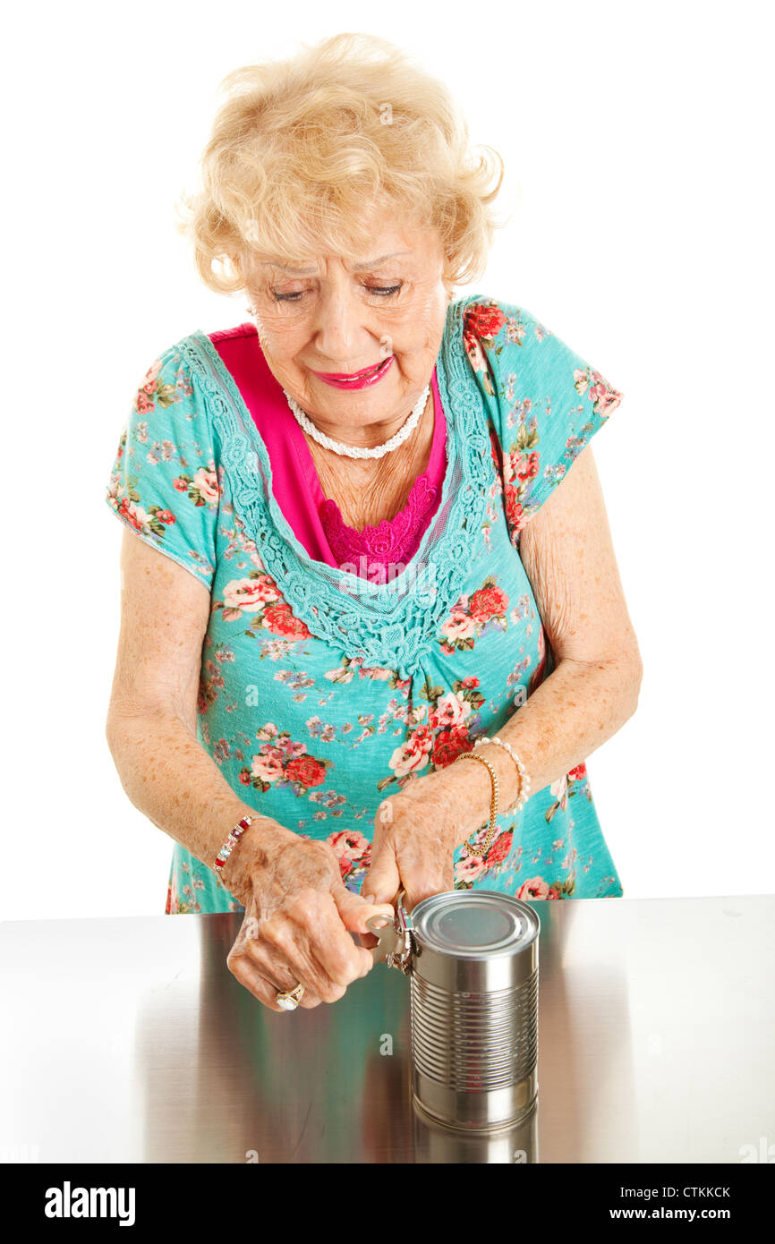 Senior woman with arthritis struggles to open a can.  - Stock Image