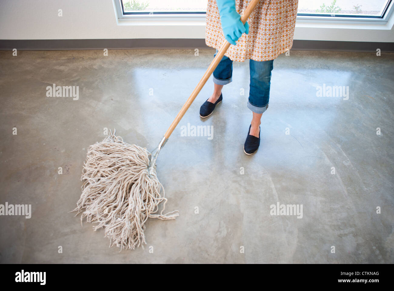Woman cleaning a concrete floor with a wet mop, wearing apron and latex gloves. - Stock Image