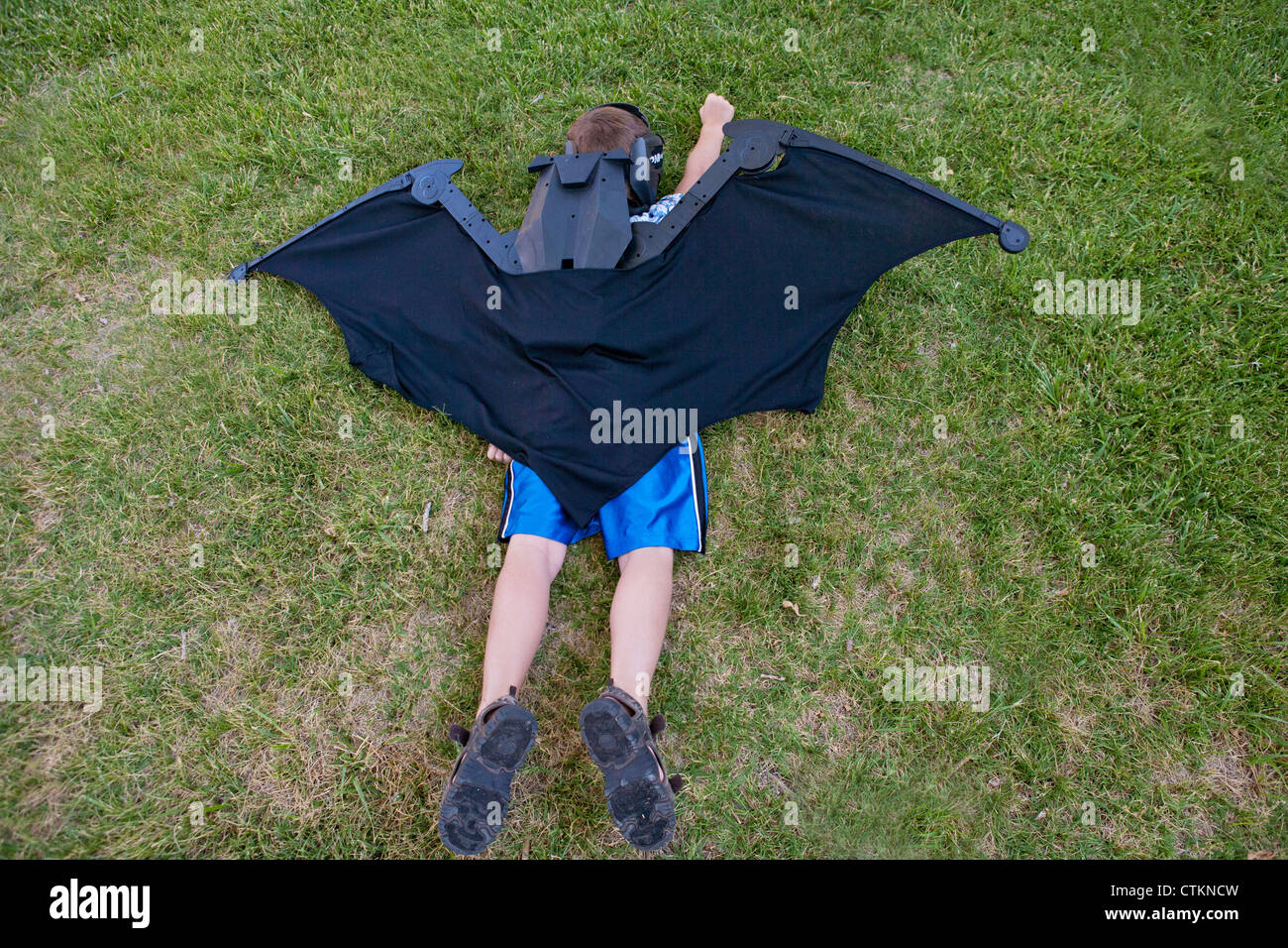 Boy pretending to be Batman, wearing giant wings, pretends to fly while laying in the grass. - Stock Image
