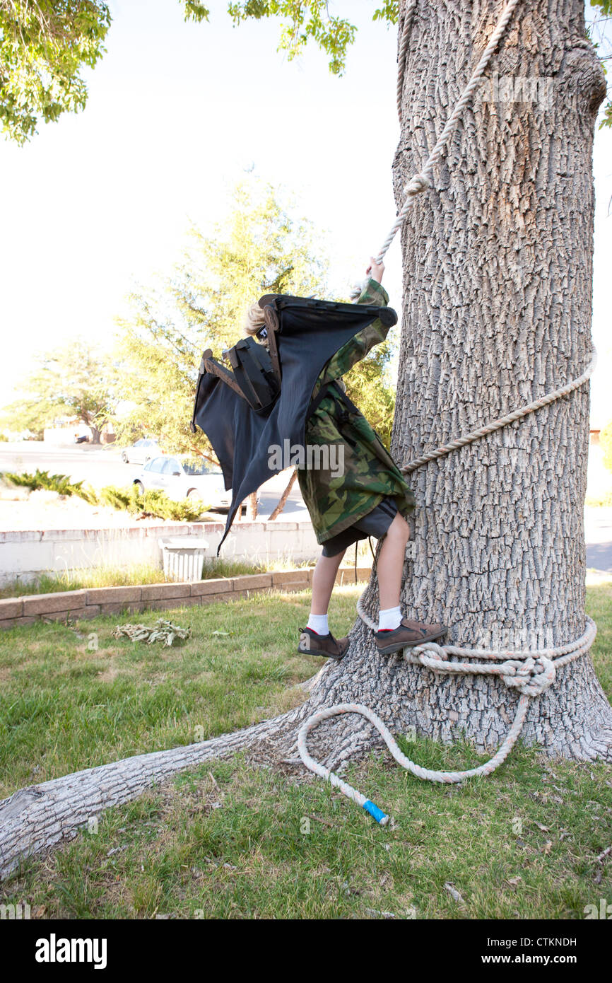 Eight year old boy pretending to be Batman, climbing a tree using a rope. - Stock Image