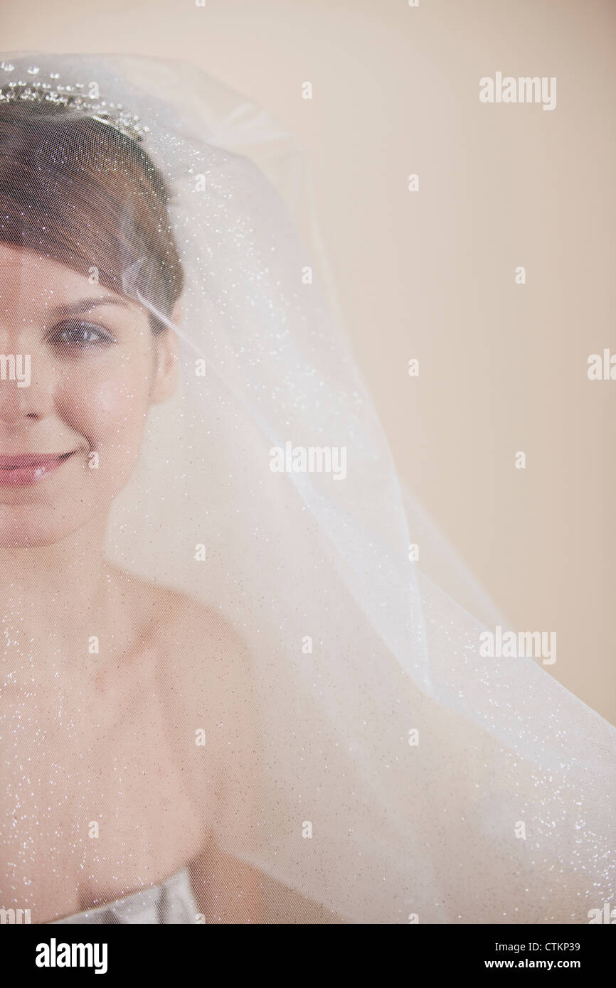 A young bride wearing a tiara and veil, left side of face - Stock Image