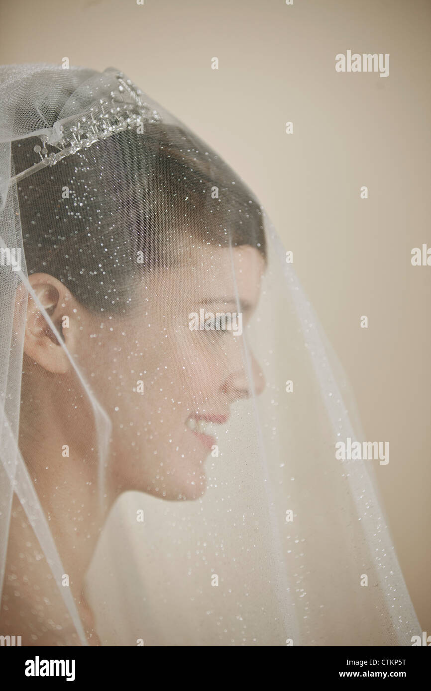 A young bride wearing a tiara and veil smiling, side view Stock Photo