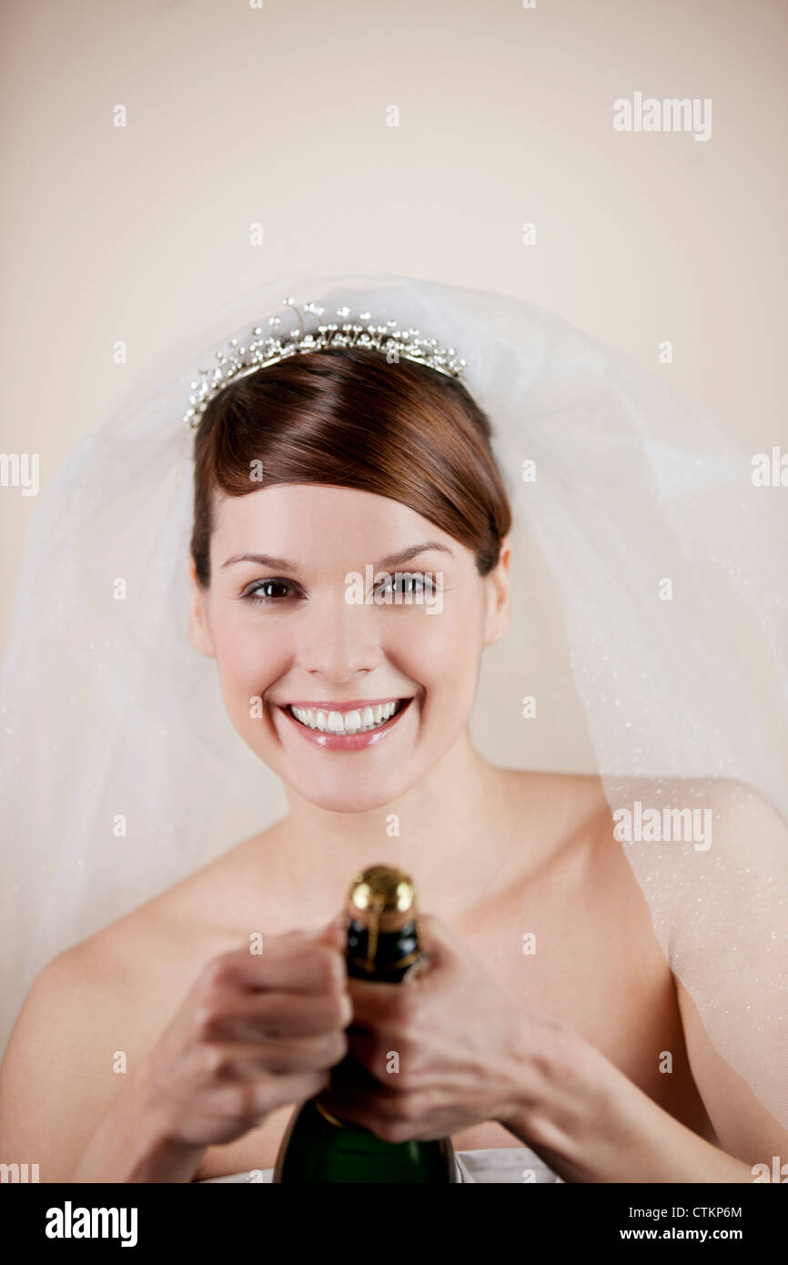 A young bride opening a bottle of champagne - Stock Image