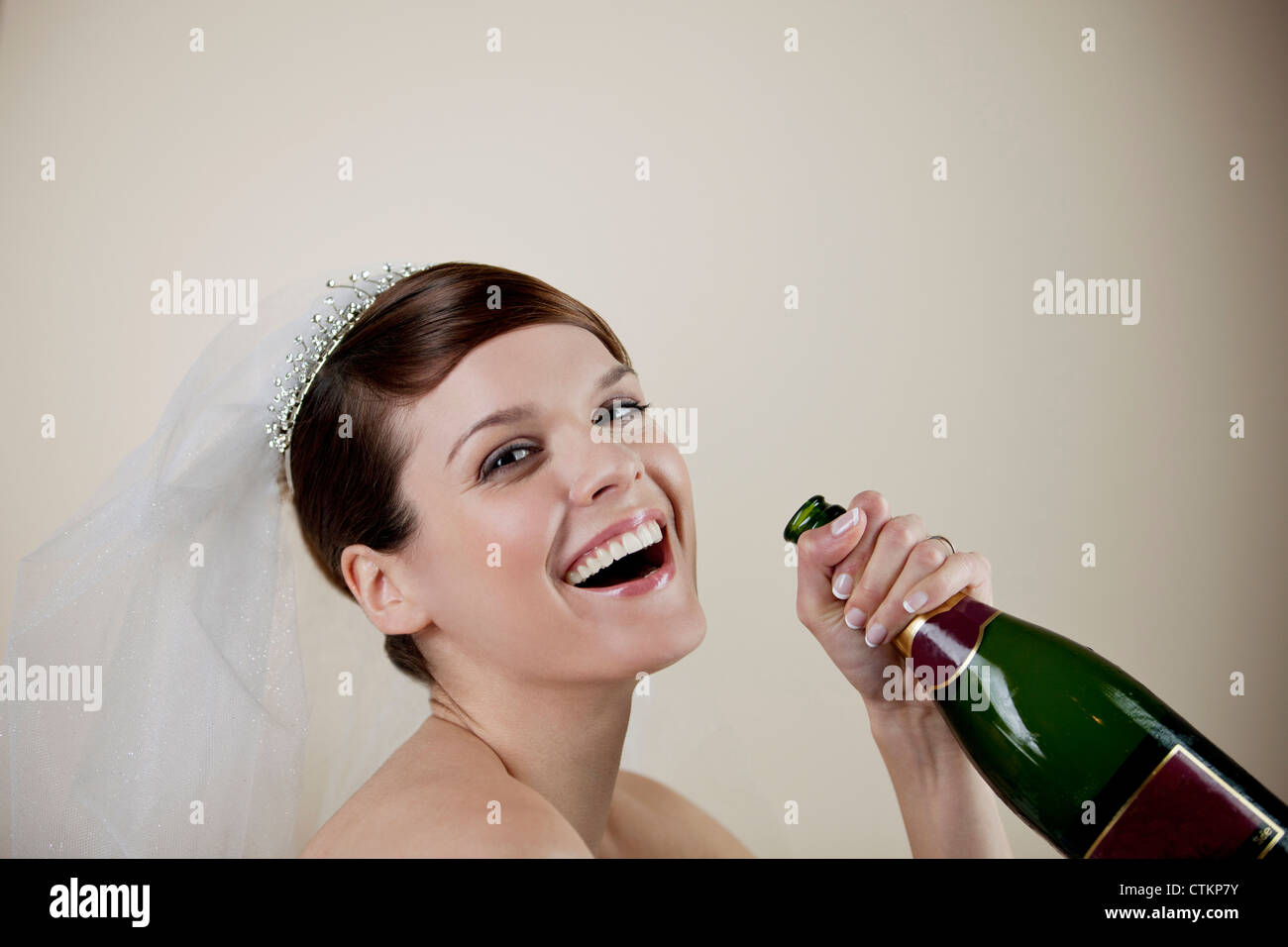 A young bride holding a bottle of champagne - Stock Image