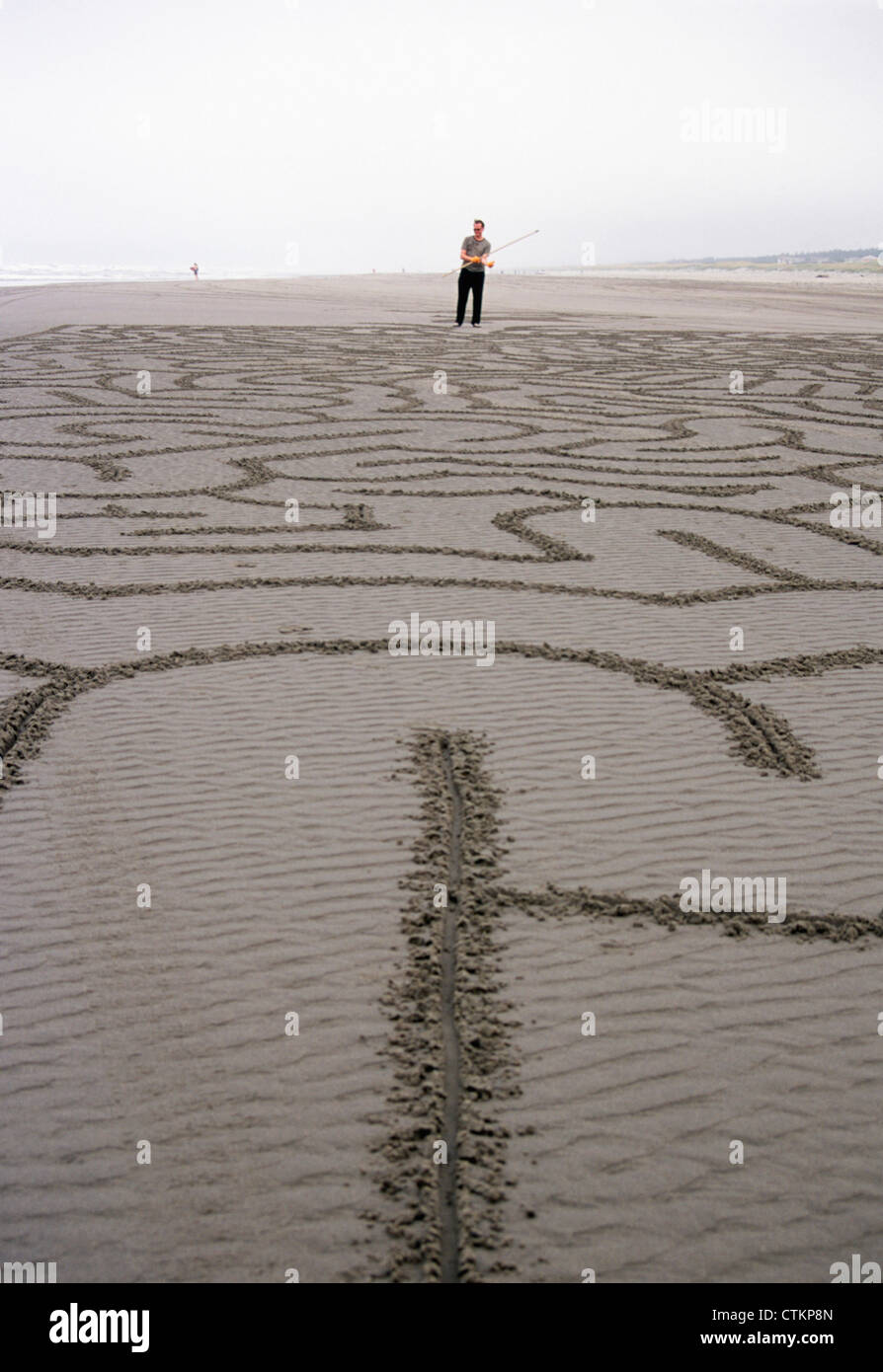 A man standing next to his completed beach maze Stock Photo