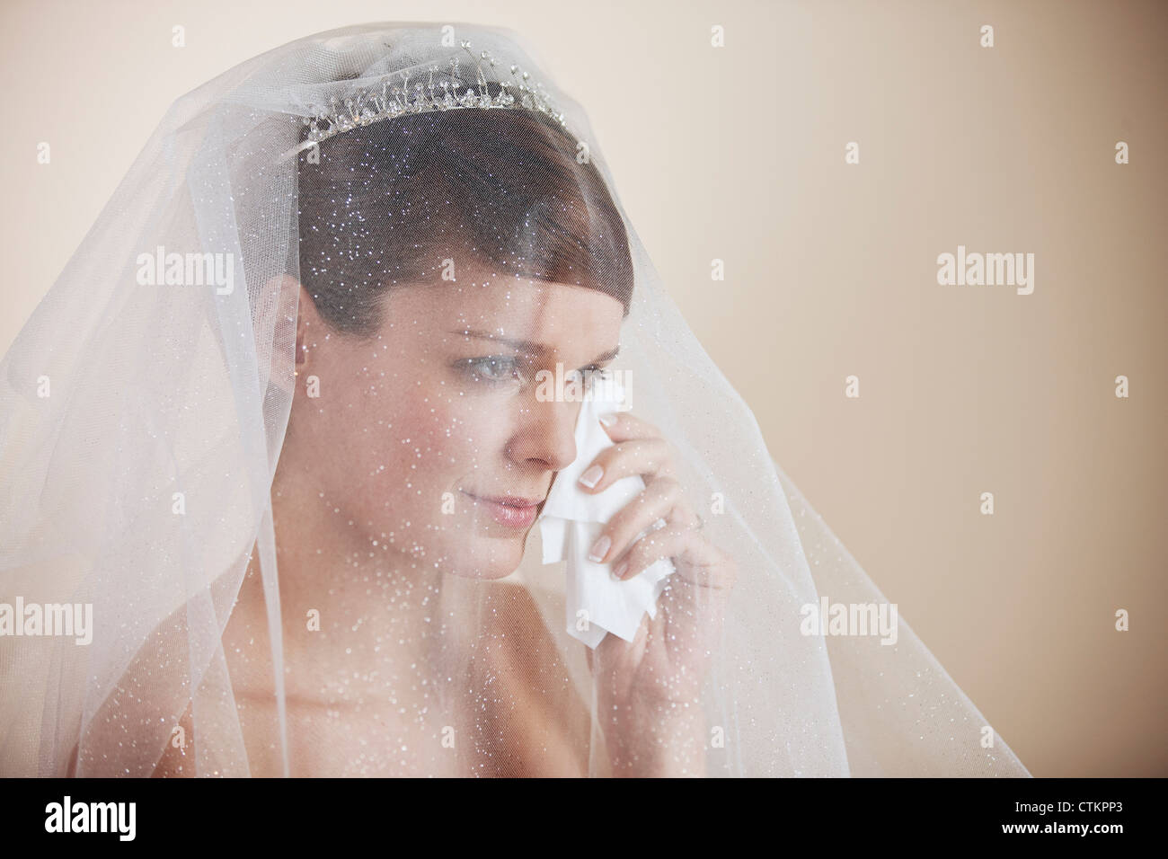 A young bride wiping tears from her face with a tissue - Stock Image
