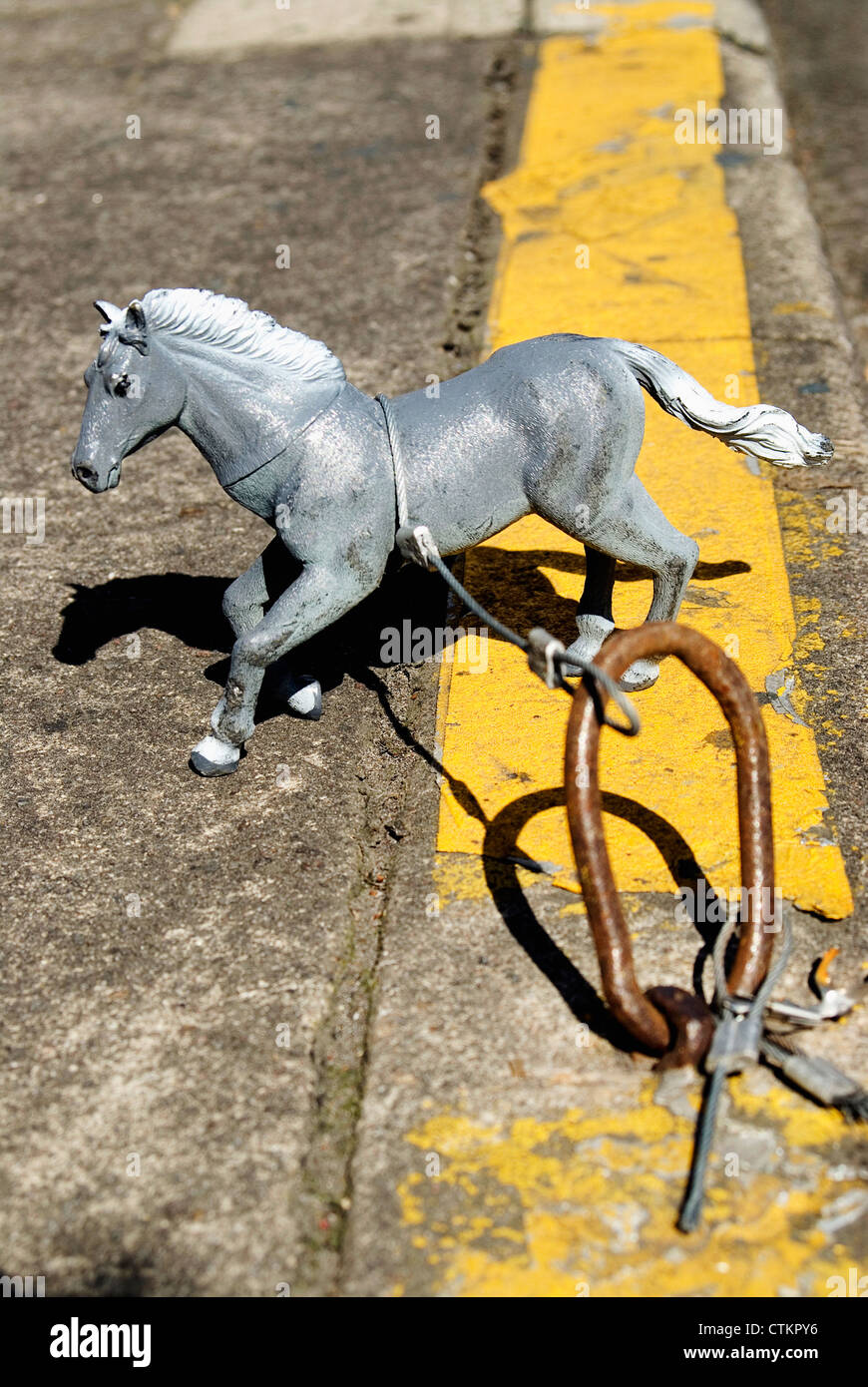 A toy horse tied up to an old horse tie in Portland, Oregon. Known as the 'horse project' taking place all - Stock Image