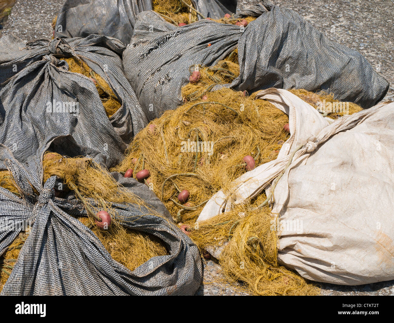 Fishing nets wrapped up in sacs - Stock Image
