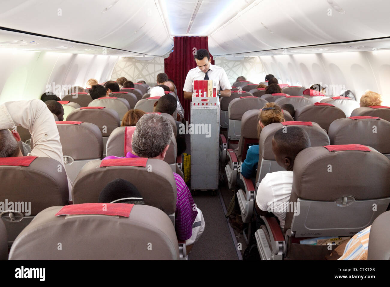 Air crew selling duty free goods in flight interior of a plane ...