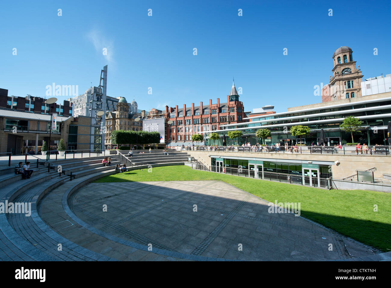 People enjoy themselves in a small amphitheatre behind Peter Street in Manchester on a sunny summer's day. - Stock Image