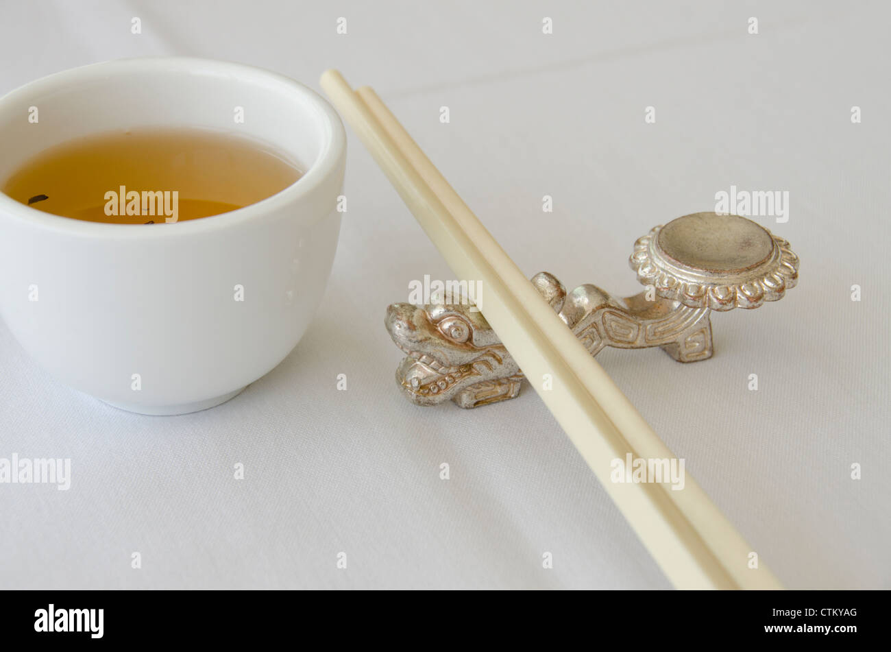 Canada, Ontario, Toronto. Detail of Chinese restaurant table, hot tea and chop sticks on silver dragon rest. Stock Photo