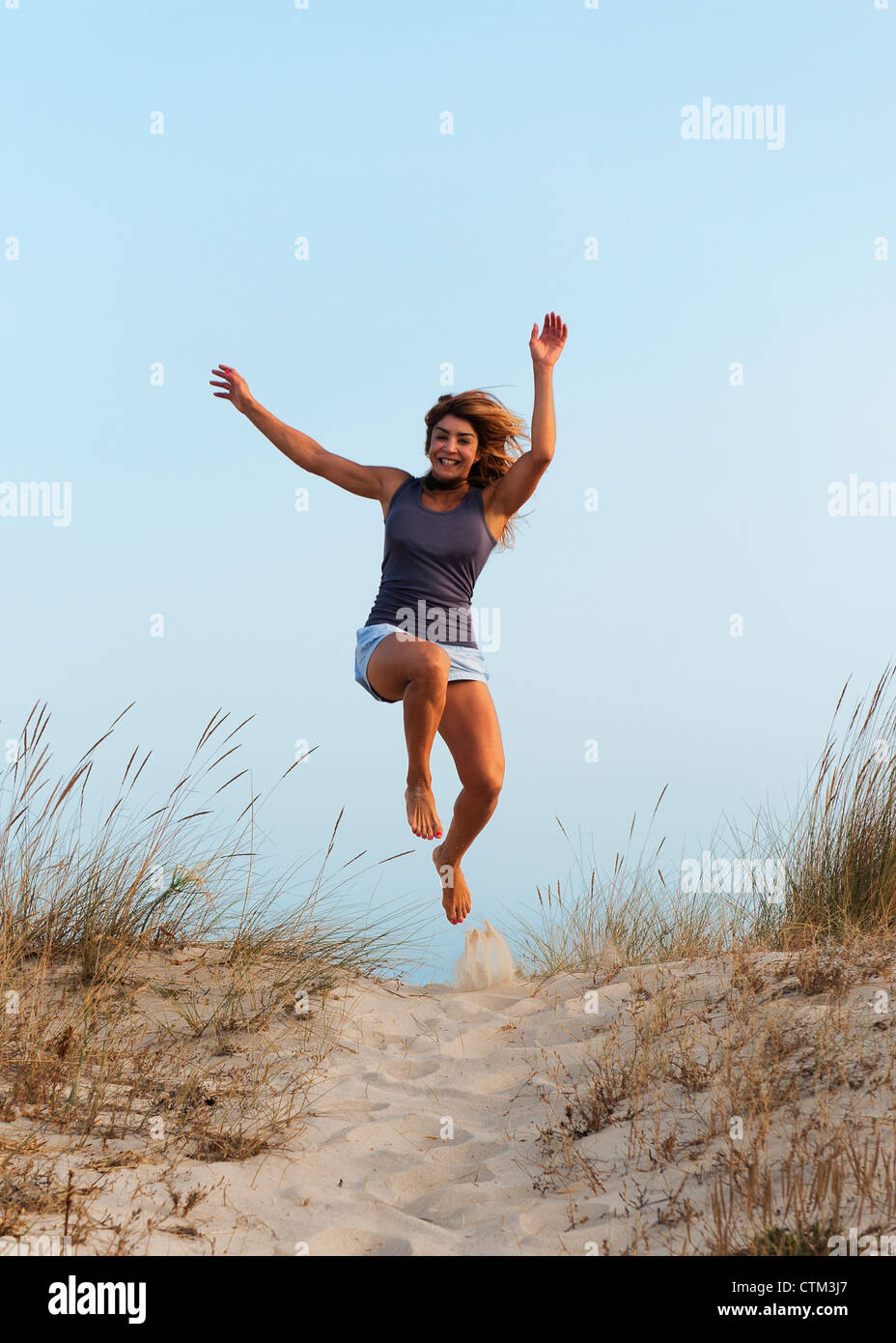A Young Woman Running And Leaping Down A Sandy Path; Tarifa, Cadiz, Andalusia, Spain - Stock Image