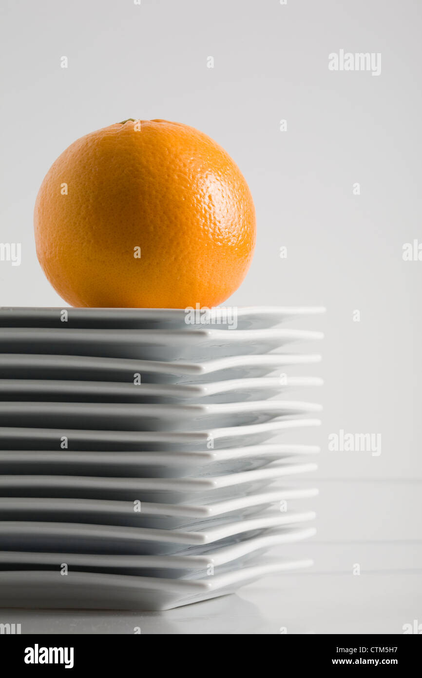 Stack Of White Square Plates With An Orange On Top On A White Stock ...