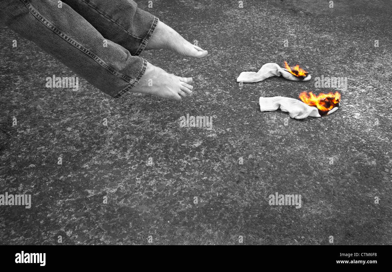 Two socks burning with two bare feet inches away. The flames are in color while the rest of the image is in black - Stock Image