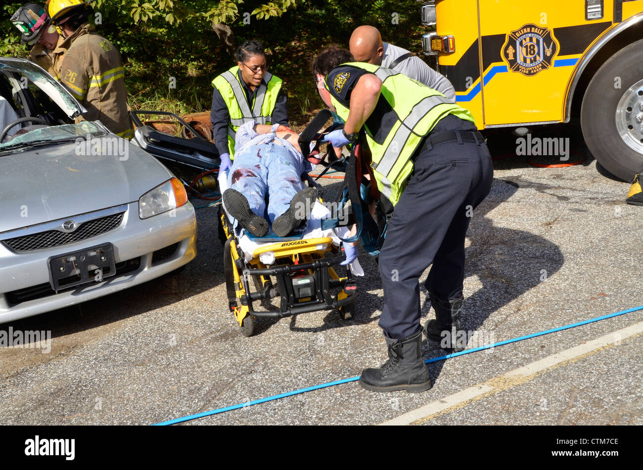Rescuers rush a badly injured woman to a waiting ambulance in Glendale, Maryland - Stock Image