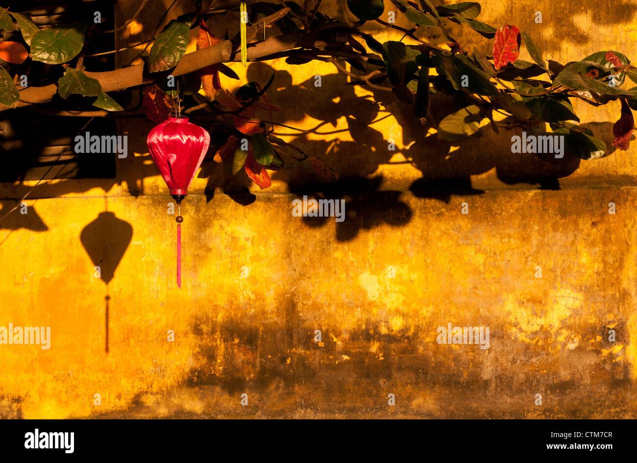 Red silk lantern on an ochre wall, late afternoon, Hoi An, Viet Nam - Stock Image